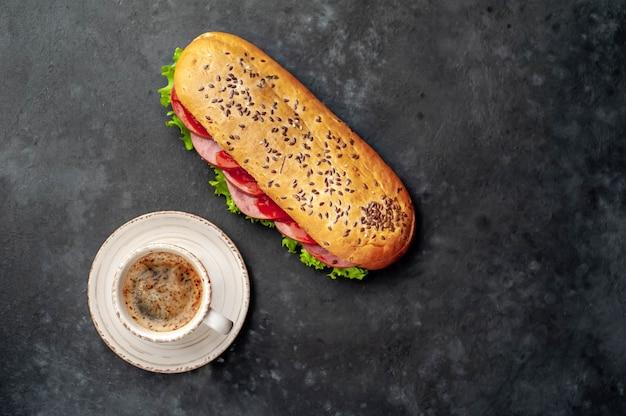 コーヒーとソーセージ、チーズ、石の背景にサラダのサンドイッチ。あなたのテキストのコピースペースの朝食コンセプト