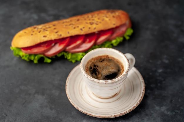 コーヒーとソーセージ、チーズ、石の背景にサラダのサンドイッチ。朝食のコンセプト