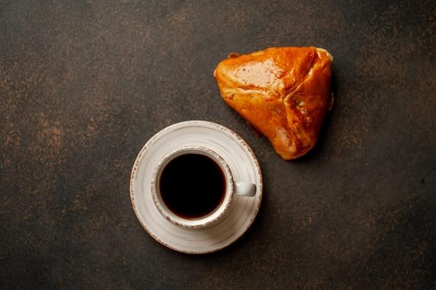 Кофе и хлебобулочные изделия на фоне камень. вкусный завтрак