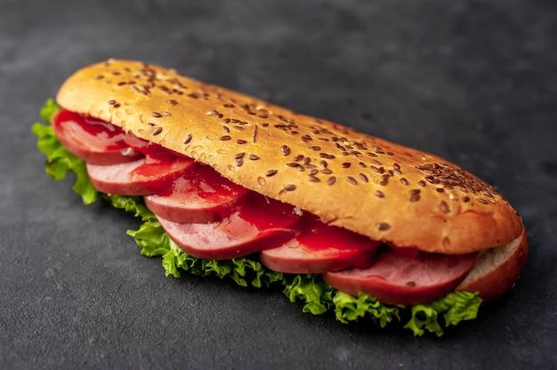 ソーセージ、チーズ、サラダ、石の背景にサンドイッチ。
