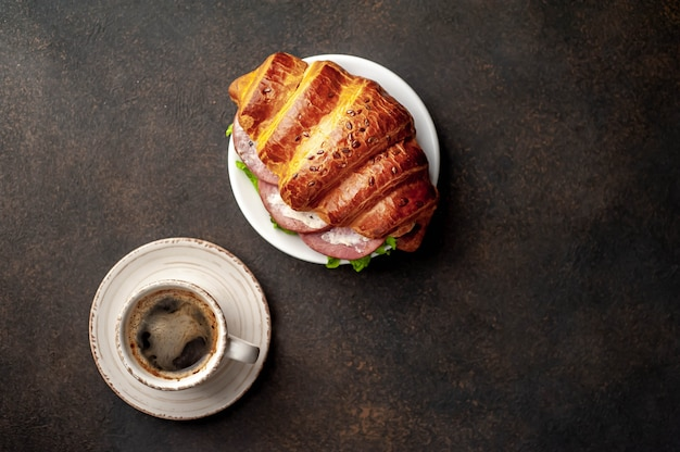 コーヒーとクロワッサン、ソーセージ、チーズ、サラダ、石の背景。あなたのテキストのコピースペースの朝食コンセプト