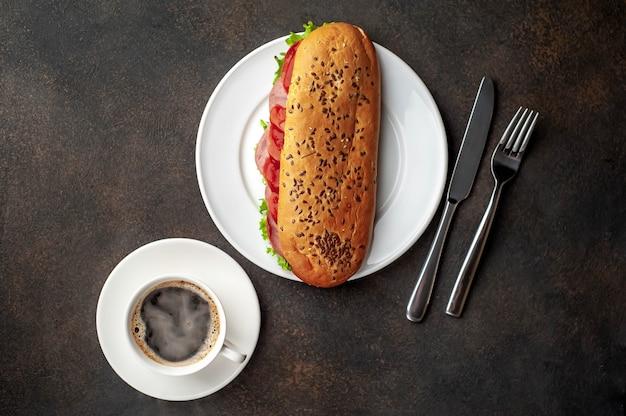 コーヒーとソーセージ、チーズ、石の背景にサラダのサンドイッチ。あなたのテキストのコピースペース