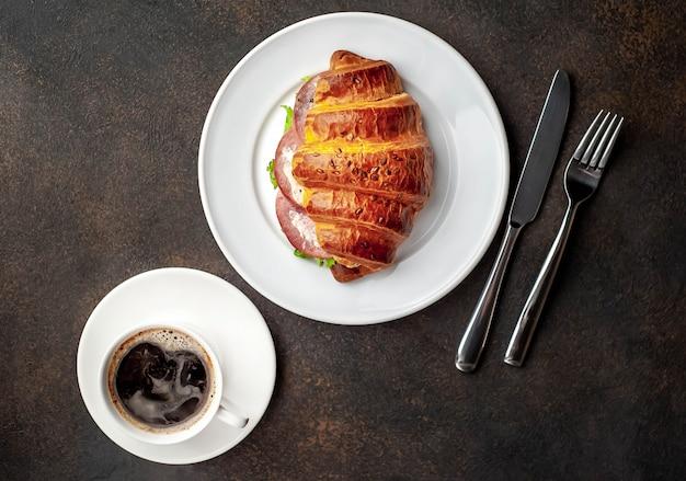 コーヒーとクロワッサン、ソーセージ、チーズ、サラダ、石の背景。朝食のコンセプト