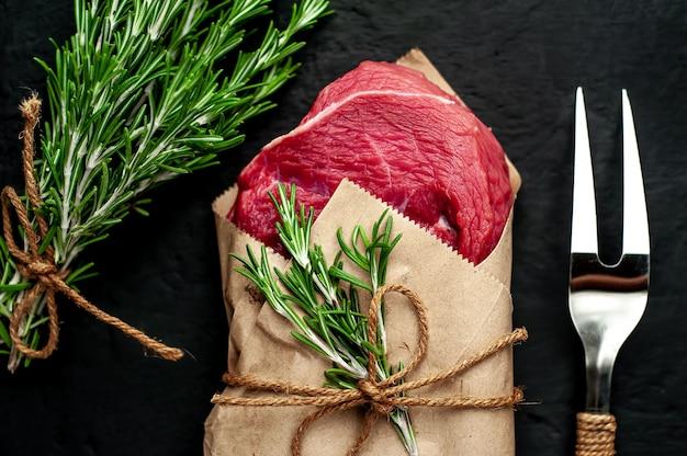 Мясо из мясной лавки, завернутые в бумагу. кусок говядины на бетон черный с разными специями