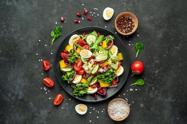 ザクロ、トマト、新鮮なキュウリ、タマネギ、ゴマ、カシューナッツ、石の背景にスパイスのサラダ。健康的なベジタリアン料理。