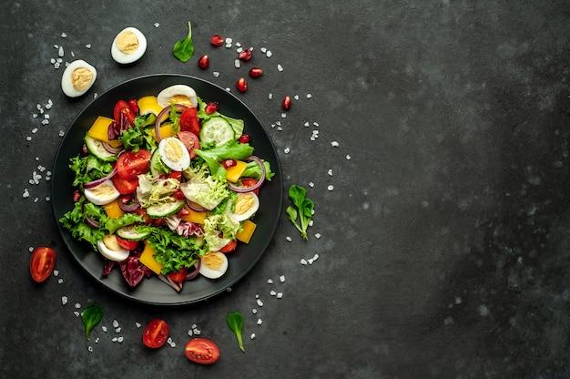 ザクロ、トマト、新鮮なキュウリ、タマネギ、ゴマ、カシューナッツのサラダ、テキストのコピースペースを持つ石の背景にスパイス