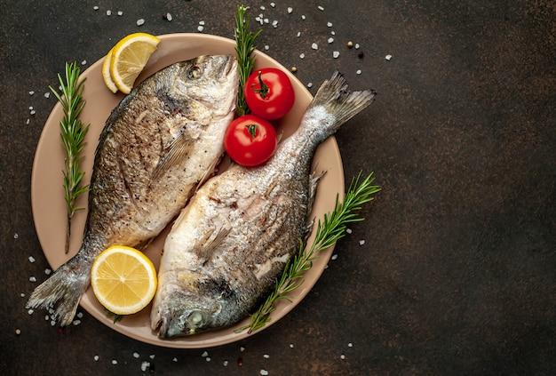 ドラド魚のグリルとフライドポテトスパイスと皿の上のフライドポテトとレモン、石の背景にテキストのコピースペース