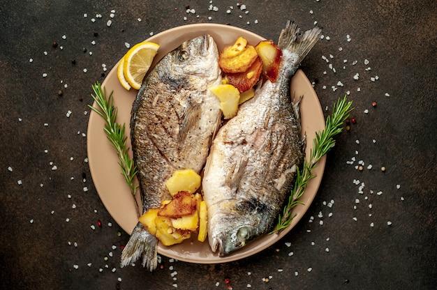 ドラド魚のグリルと石の背景にレモンとスパイスが香る皿にフライドポテト