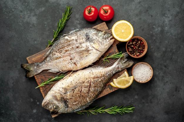 スパイスと石の背景にレモンとまな板の上のドラド魚のグリル