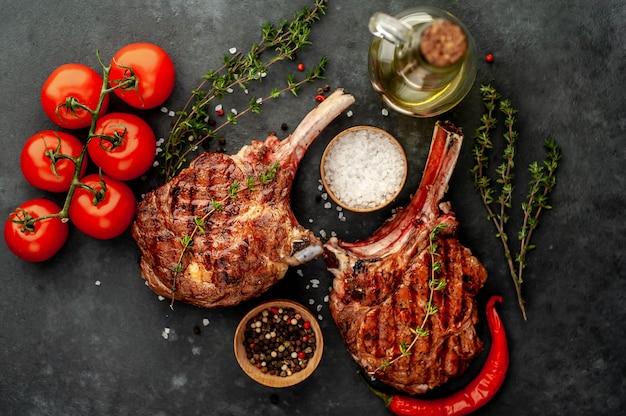 ステーキ-スパイス、牛肉のトマホークのグリル、石の背景にタイム。あなたのテキストのコピースペース
