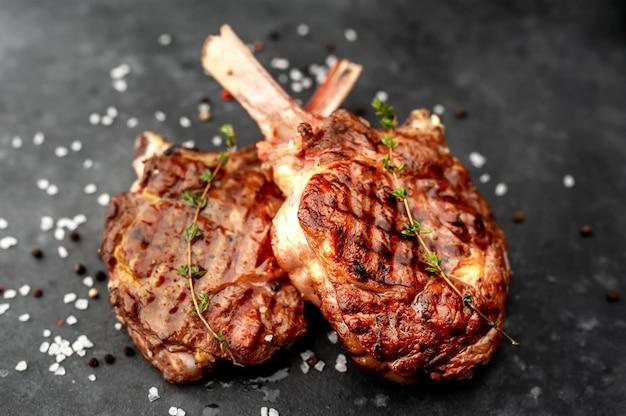 ステーキ-スパイス、牛肉のトマホークのグリル、石の背景にタイム。
