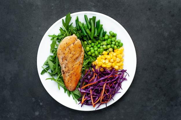 健康的な栄養。鶏の胸肉、ルッコラ、赤キャベツ、にんじん、トウモロコシ、グリーンピース、インゲン、白いプレート