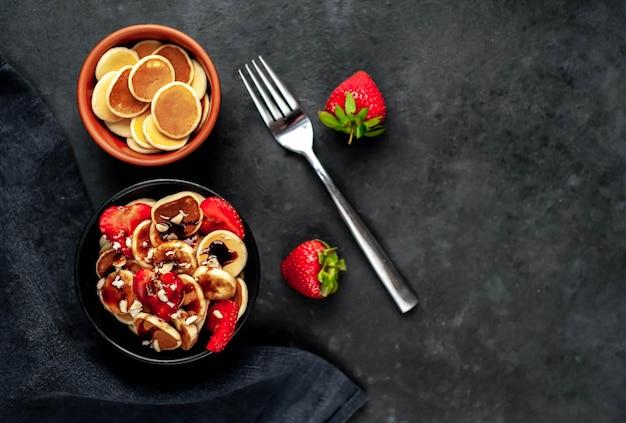 テーブルの上の皿にイチゴとバナナのミニパンケーキ