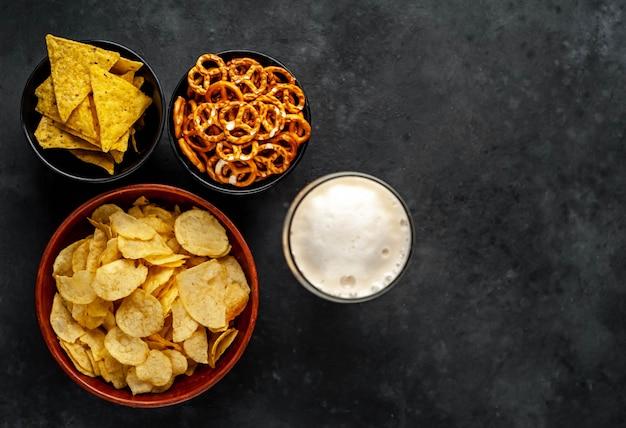 Разные закуски в мисках и пиво на столе