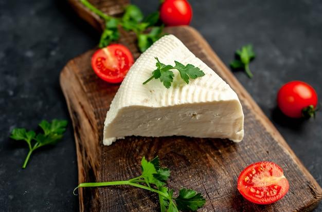 Сыр фета с помидорами черри на разделочной доске