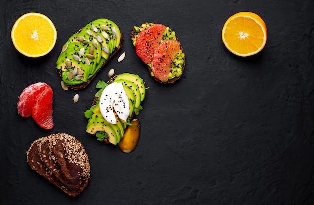 Тосты с авокадо, кунжутом, грейпфрутом, апельсином, яйцом и кофе на бетонном черном фоне. вкусный завтрак с кофе и тостами