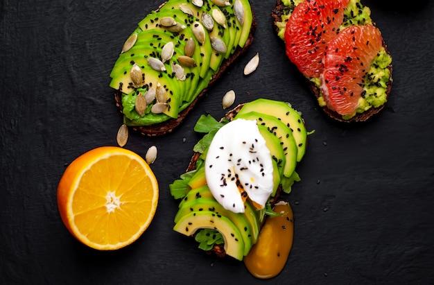 Тосты с авокадо, кунжутом, грейпфрутом, апельсином, яйцом на каменном фоне