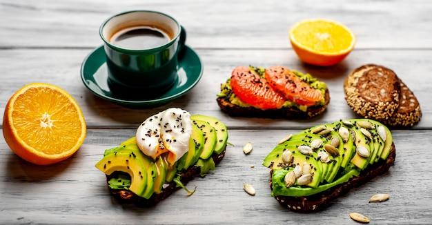 Тосты с авокадо, кунжутом, грейпфрутом, апельсином, яйцом и кофе на фоне дерева. вкусный завтрак с кофе и тостами