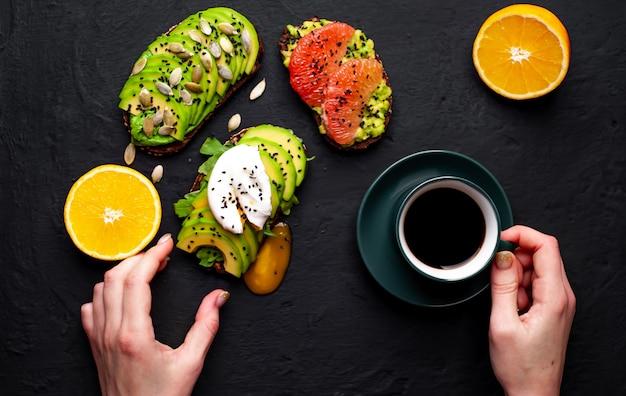 Тосты с авокадо, кунжутом, грейпфрутом, апельсином, яйцом и кофе на фоне камня. вкусный завтрак с кофе и тостами