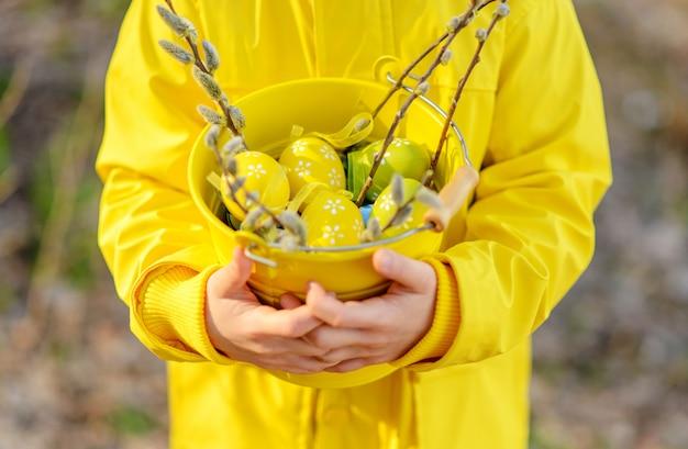 Маленький мальчик в ярко-желтом плаще держит пасхальные яйца в корзину, крупным планом, концепция пасхи