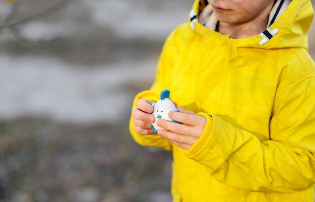 Маленький мальчик в ярко-желтом плаще, играя с пасхальными яйцами на природе, концепция пасхи