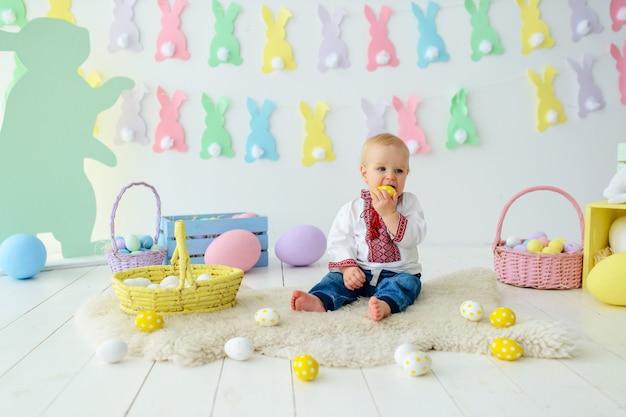 Милый улыбающийся малыш в традиционной вышивке в разноцветных пасхальных декорациях
