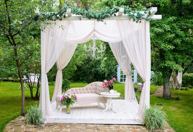 緑豊かな庭園の夏の繊細なエレガントなガゼボ。新鮮な庭の白いカーテンとガゼボの花で飾られた絶妙な古典的なソファ