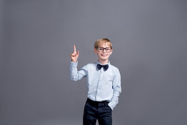 灰色のポーズのメガネの少年