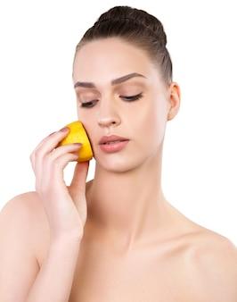 健康新鮮な肌とレモンの孤立した美しい若い女性。自然美容トリートメント