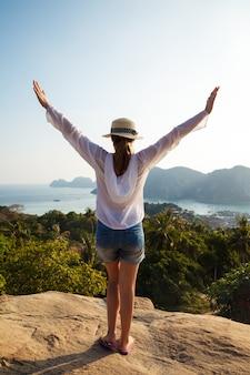 海沿いの素晴らしい景色を楽しむ若い女性旅行者