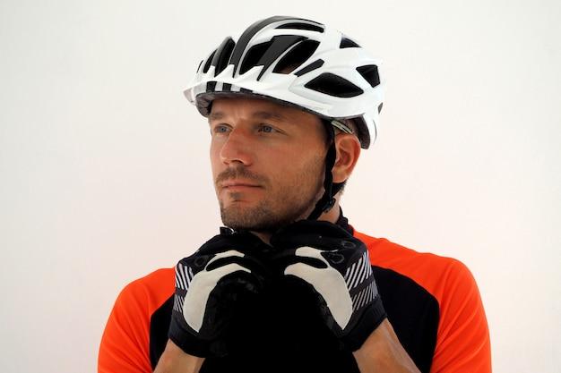 ジャージのサイクリストがヘルメットのストラップを締めます。肖像画を閉じます。
