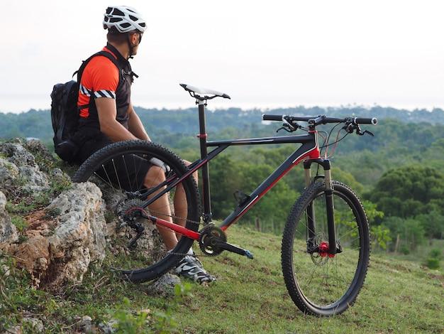 アクティブなライフスタイル。サイクリストは日の出の自然の中でレクリエーションをお楽しみください。丘の上のサイクリスト。