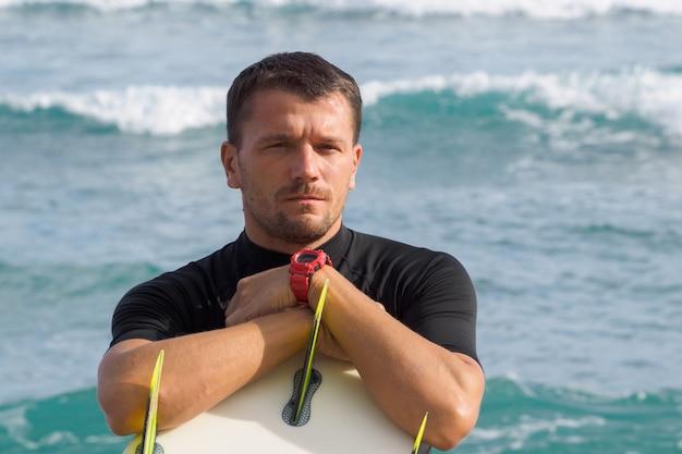 サーフボードを保持しているサーファーの肖像画。海洋 。