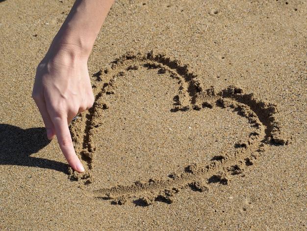 Сердце, рисование пальцем в песке. женская рука.