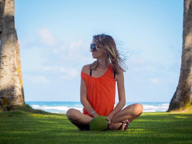Маленькая девочка на каникулах на тропическом острове, сидя на зеленой траве около зеленого кокоса. океан