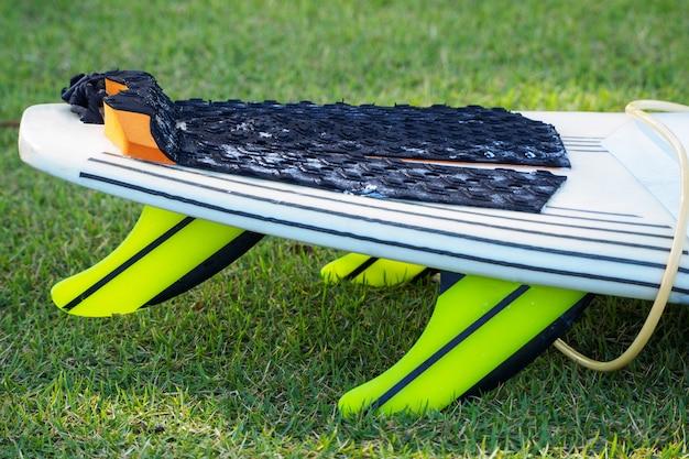 黄色のひもと緑のサーフボードフィン。緑の草の上に横たわる。