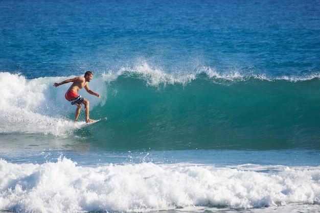 完璧なトロピカルブルーウェーブに高速で乗るサーファー。海で波をキャッチする男性。