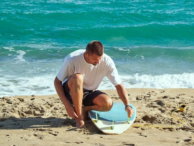 サーフボードにフィンを置くサーファー。サーフセッションのためのサーフボードの準備。