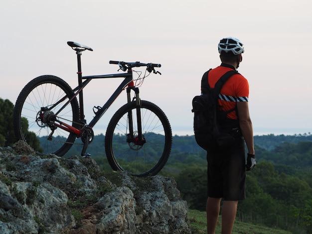丘の上にサイクリストが立ち、夕暮れ時にマウンテンバイクを持ちます。大西洋の地平線上。アクティブなライフスタイル。