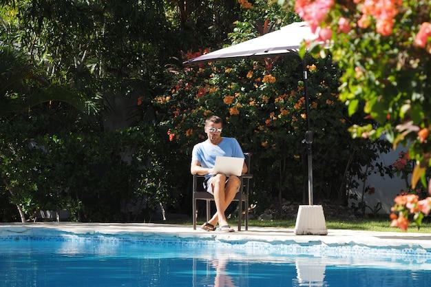 フリーランスのコンセプト。暖かい気候のラップトップを持った男がプールの近くに座って働いています。庭の周り。