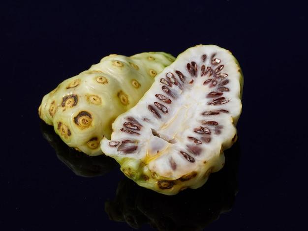 Половина свежих фруктов нони