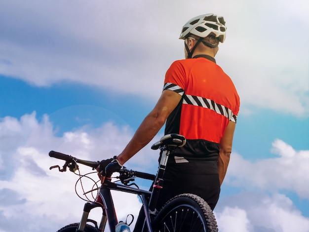 Велосипедист стоит на вершине горы возле горного велосипеда
