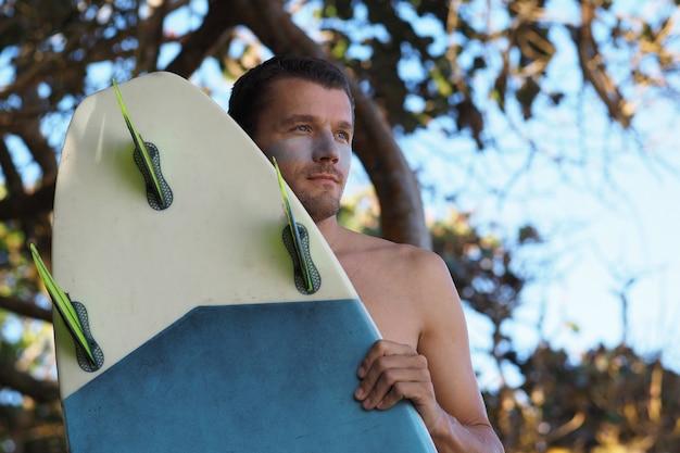 ライフスタイルのイメージ。サーフボードで若いサーファーの肖像画を閉じます。
