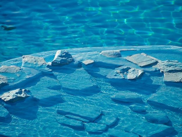 Бассейн с камнем в воде.