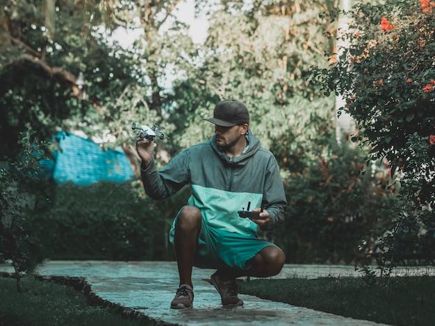 カラフルなパーカーの男は、彼の手で小さなコンパクトなドローンとリモコンを保持しています。熱帯の休暇。トーンの画像。