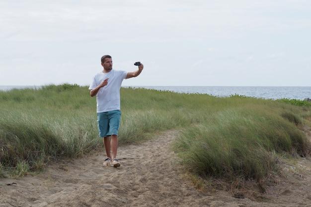 Человек видео блоггер идет по пути в зеленой траве возле океана. тропический остров, береговая линия. стиль жизни.