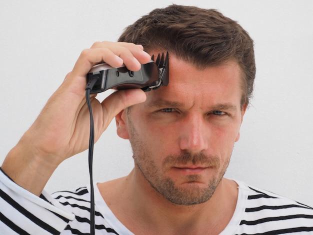 Человек стричь свои волосы с помощью машинки. образ жизни.