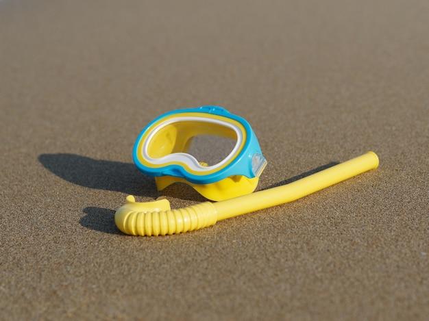 黄色のダイビングマスクとビーチの砂の上のシュノーケル。上面図。