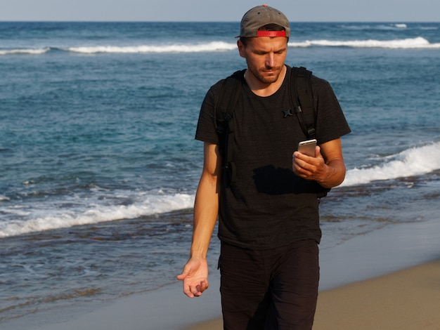 ライフスタイルイメージ。日焼けした男が驚いた表情で携帯電話を見ている。熱帯のビーチを歩いています。
