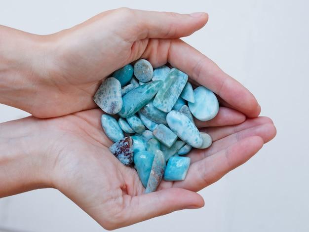 Полированные ларимар камни в руках женщины. вид сверху.